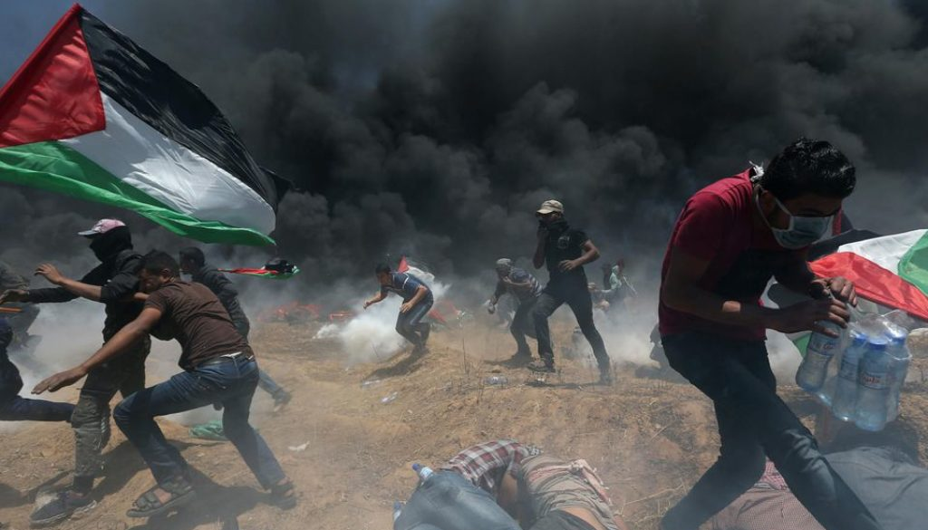1121599-palestinian-demonstrators-run-for-cover-from-israeli-fire-and-tear-gas-during-a-protest-against-us-e