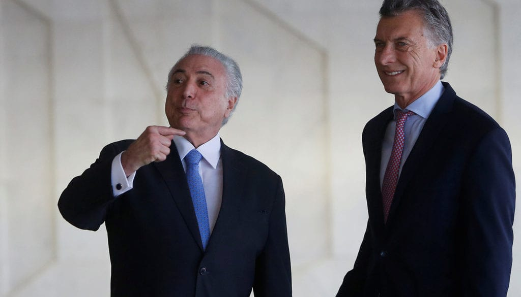 Brazil's President Michel Temer reacts next to Argentina's President Mauricio Macri before a working session at Mercosur trade bloc annual summit in Brasilia