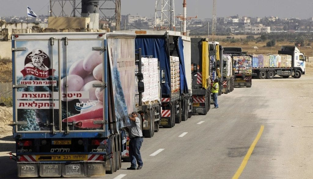 Trucks carrying food supplies wait to cross into Gaza through Sufa border crossing