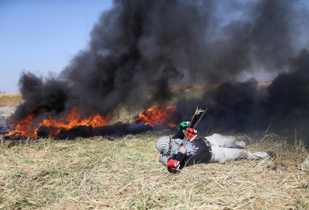 A Palestinian hurls stones at Israeli troops during clashes at the Gaza-Israel border at a protest demanding the right to return to their homeland, in the southern Gaza Strip March 31, 2018. REUTERS/Ibraheem Abu Mustafa