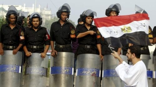 A man waves an Egyptian flag in front of riot police during Eid al-Fitr celebrations on Tahrir square in Cairo