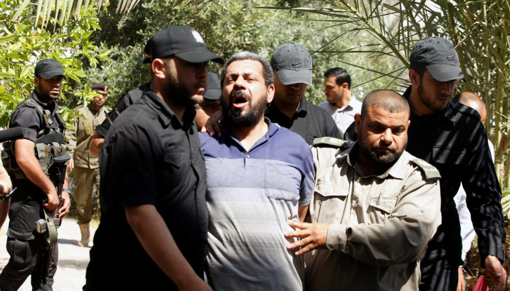 Members of Palestinian security forces loyal to Hamas escort an alleged collaborator with Israel, who was convicted in participating in killing senior Hamas commander Mazen Fuqaha, as he arrives to a Hamas-run military court in Gaza City
