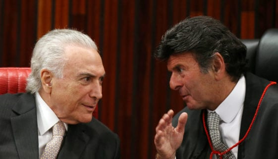 Judge Luiz Fux listens to the Brazil's President Michel Temer, as he takes office as president of the Superior Electoral Court in Brasilia