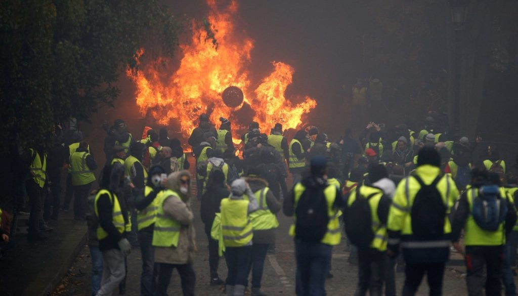 Protesters wearing yellow vests, a symbol of a French drivers' protest against higher diesel taxes, stand near a burning car during clashes near the Place de l'Etoile in Paris