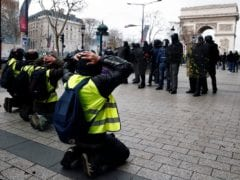 "Protesters wearing yellow vests kneel along the Champs-Elysees Avenue near the Arc de Triomphe as they face off with French riot police during a national day of protest by the ""yellow vests"" movement in Paris"