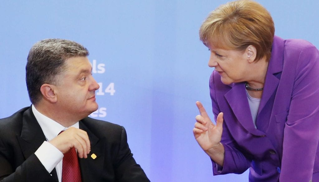 Ukraine's President Poroshenko listens to Germany's Chancellor Merkel during signing ceremony of cooperation agreement in Brussels