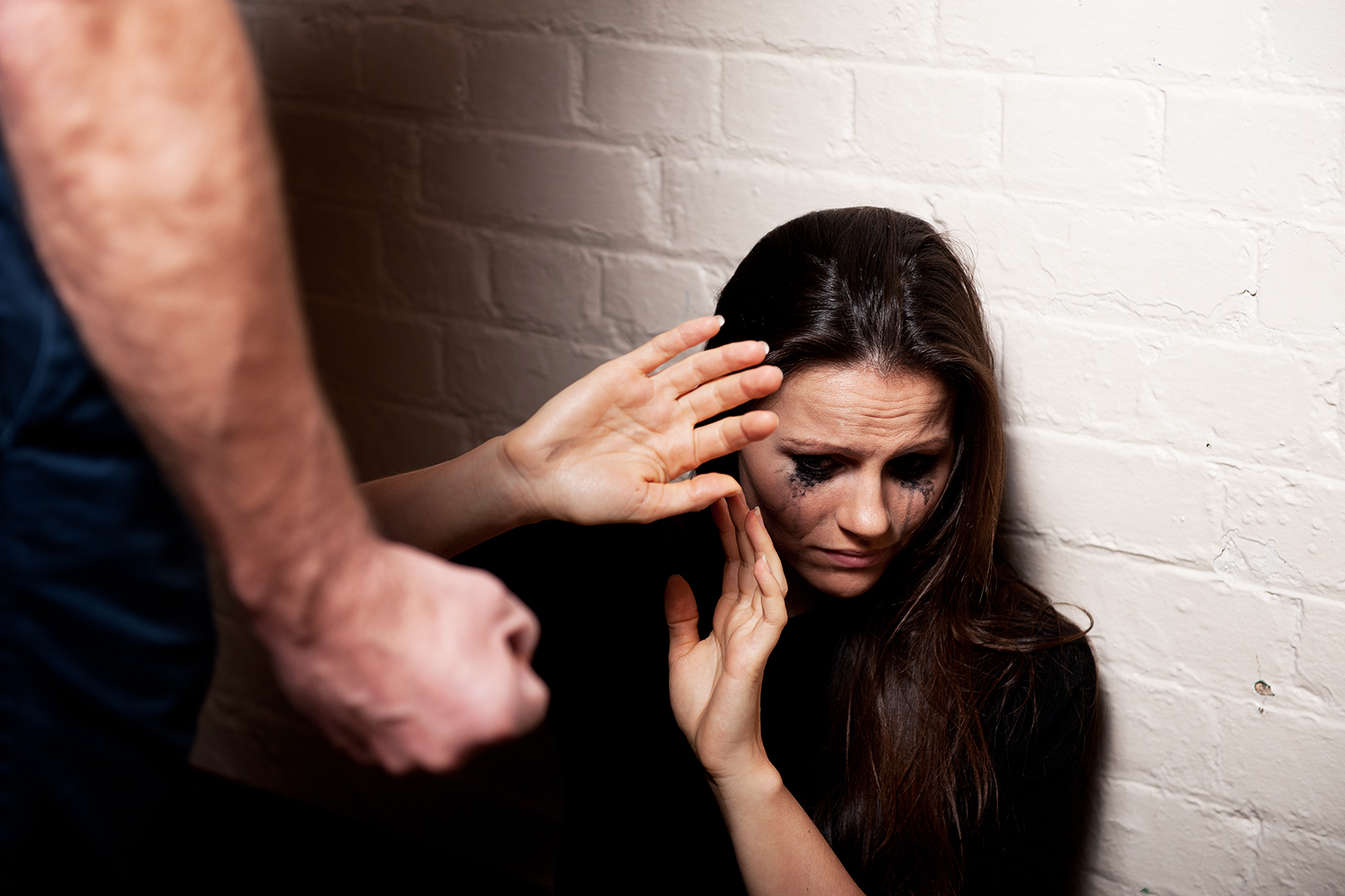 Young woman trying to protect herself from a man's clenched fist.
