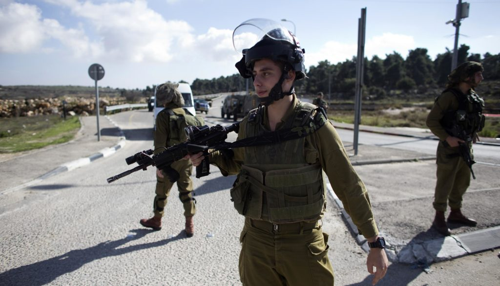 Israeli soldiers stand at the scene of a stabbing attack near the West Bank Jewish settlement of Efrat