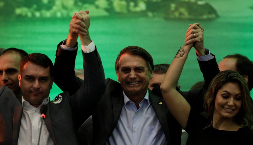 Federal deputy Bolsonaro holds his hands up with his son and wife during the national convention of the Party for Socialism and Liberation (PSL) where he is to be formalised as a candidate for the Presidency of the Republic, in Rio de Janeiro