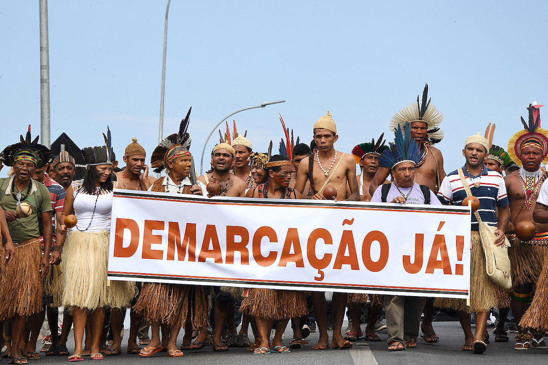 Brazilian indigenous people from several tribes protest against the new rules of demarcation of indigenous territories, in Brasilia, on November 23, 2017.  The new law underway in the Brazilian National Congress increases the difficulty to map new indigenous territories and reduces several areas already demarcated. / AFP PHOTO / EVARISTO SA