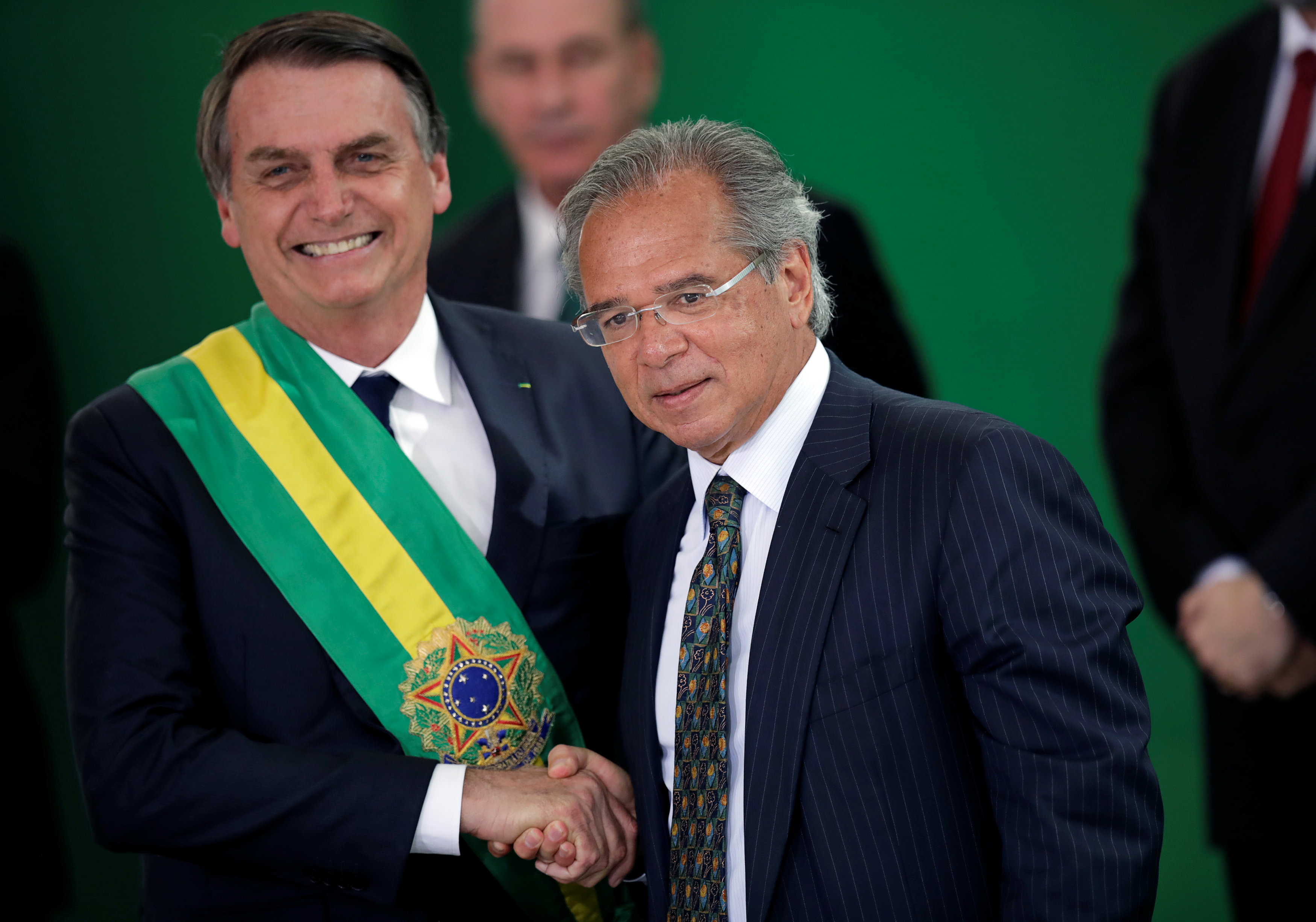 Brazil's new President Jair Bolsonaro shakes hands with PauloGuedes, incoming Brazil's Economy Minister, during a ceremony at the Planalto Palace, in Brasilia, Brazil January 1, 2019. REUTERS/Ueslei Marcelino