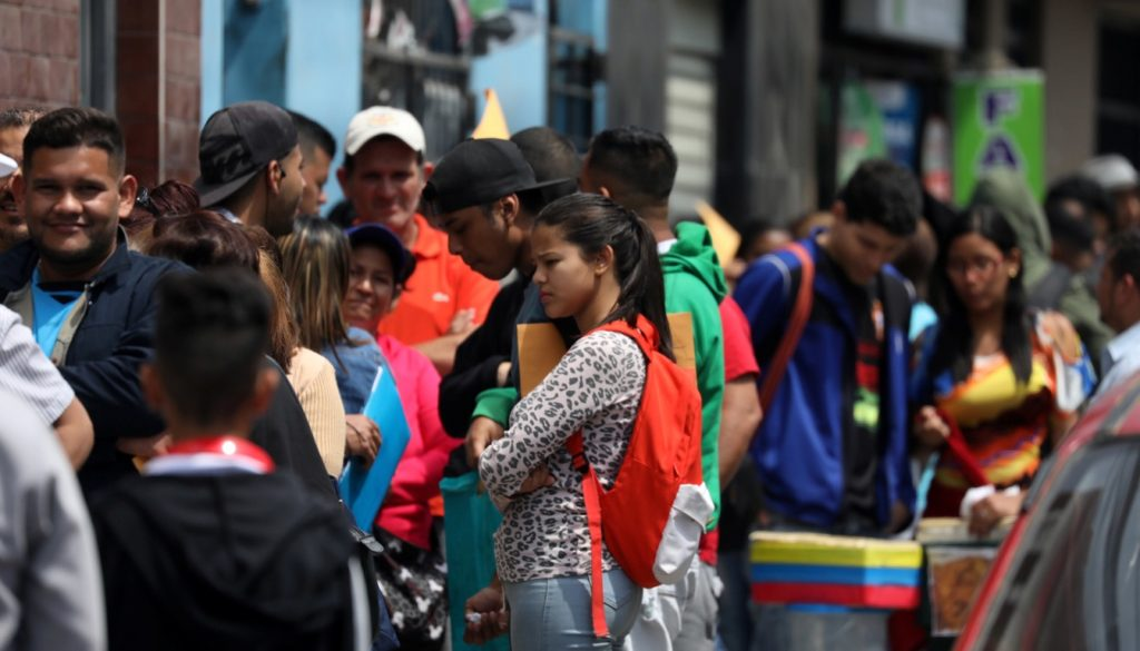 Venezuelan migrants queue to get temporary residency permits outside the immigration office in Lima
