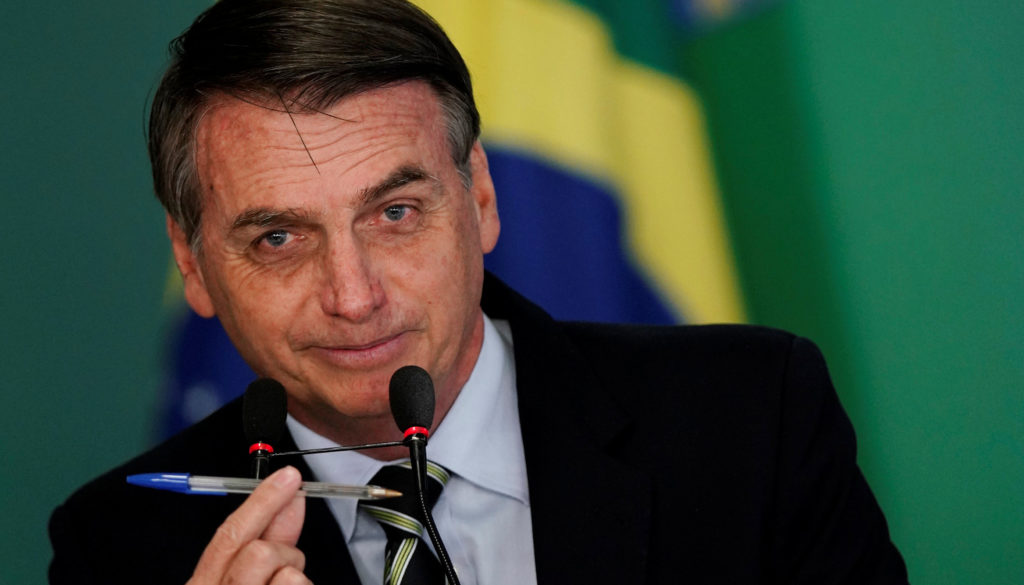 Brazil's President Jair Bolsonaro shows a pen during a signing ceremony of the decree which eases gun restrictions in Brazil, at the Planalto Palace in Brasilia