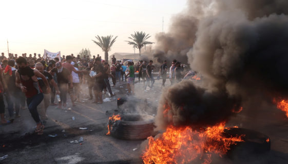 Demonstrators block the road with burning tires during a protest over unemployment, corruption and poor public services, in Baghdad
