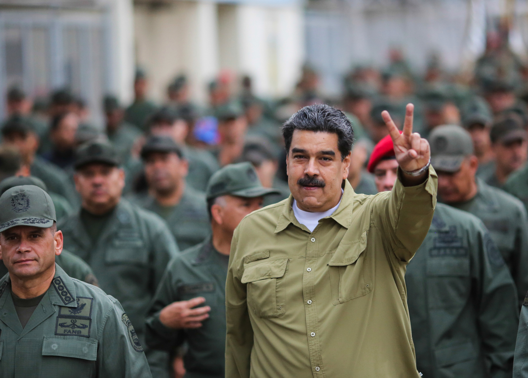 In this handout photo released by the Miraflores Presidential Press Office, Venezuela's President Nicolas Maduro flashes a V for Victory hand gesture after arriving at the Fort Tiuna military base in Caracas, Venezuela, Wednesday, Jan. 30, 2019. Since opposition leader Juan Guaido declared himself interim president last week with the support of the U.S. and other nations, Maduro has appeared almost daily on state TV with his military, projecting an image of invincibility even as international pressure against him builds. (Marcelo Garcia/Miraflores Presidential Press Office via AP)