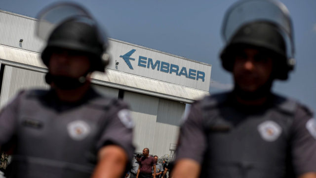 Police officers take position in front of the Embraer's plant in Sao Jose dos Campos