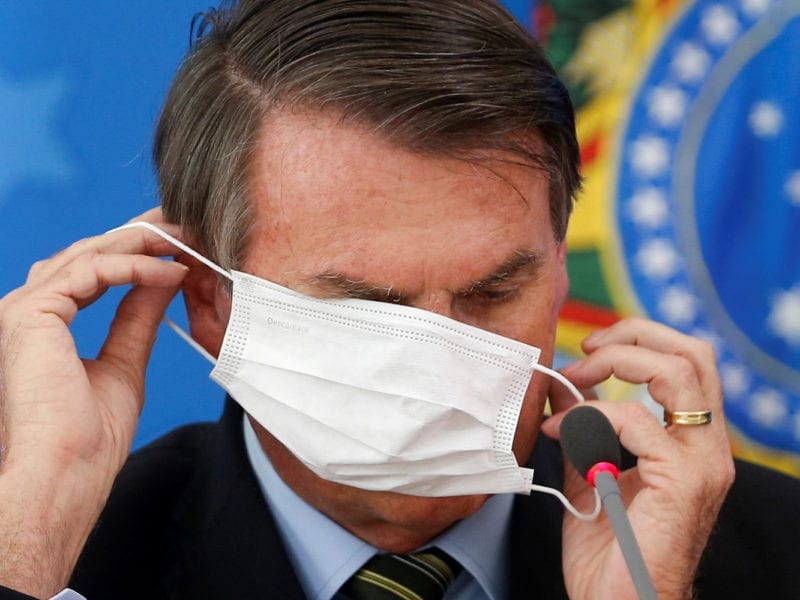 Brazil's President Jair Bolsonaro wearing a protective face masks reacts during a news conference to announce measures to curb the spread of the coronavirus disease (COVID-19) in Brasilia, Brazil March 18, 2020. REUTERS/Adriano Machado