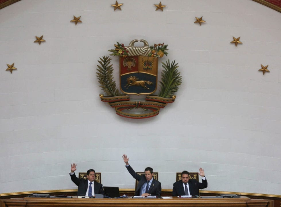 Juan Guaido, center, President of National Assembly and self-proclaimed interim president, Edgar Zambrano first Vice President, left, and Staling Gonzalez second Vice President, raise their hands to approve of daily order of business during a session of the National Assembly in Caracas, Venezuela, Tuesday, April 2, 2019. Venezuela's chief justice on Monday asked lawmakers of the rival pro-government National Constituent Assembly to strip Guaido of his parliamentary immunity, taking a step toward prosecuting him for alleged crimes as he seeks to oust President Nicolas Maduro.(AP Photo/Fernando Llano)