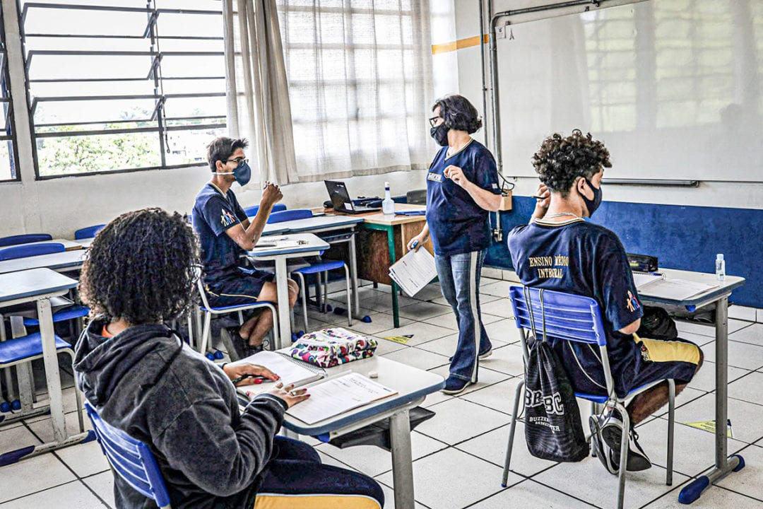 A teacher talks to a student in a classroom with desks at a social distance at Professor Milton da Silva Rodrigues school on the first day of classes of Sao Paulo state's schools amid the coronavirus disease (COVID-19) outbreak in Sao Paulo, Brazil November 3, 2020. REUTERS/Amanda Perobelli