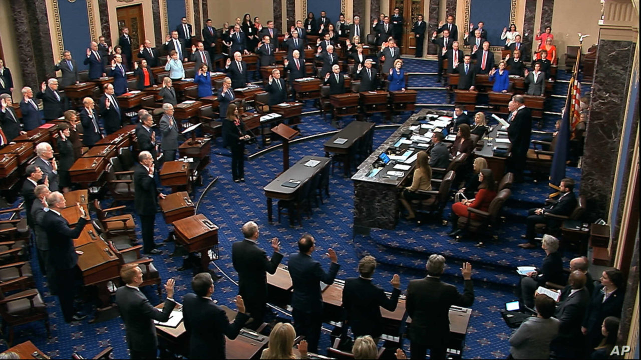 FILE - In this Thursday, Jan. 16, 2020, file image from video, presiding officer Supreme Court Chief Justice John Roberts swears in members of the Senate for the impeachment trial against President Donald Trump at the U.S. Capitol in Washington. Reporters at the Capitol want more cameras in the Senate to cover the impeachment trial and fewer restrictions to talk to senators when they are not sitting in judgment of the president. (Senate Television via AP, File)
