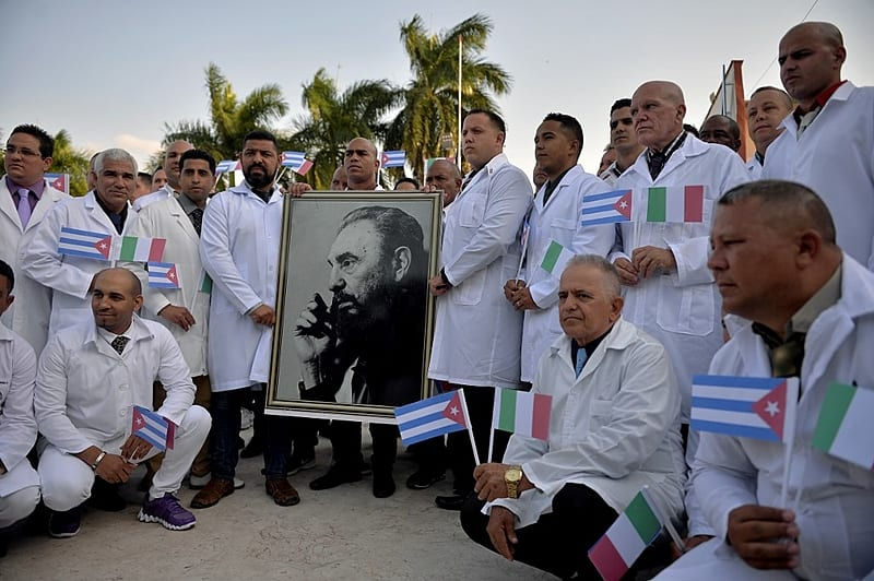 Doctors and nurses of Cuba's Henry Reeve International Medical Brigade pose with a portrait of Cuban late leader Fidel Castro as they are bid farewell before travelling to hard-hit Italy to help in the fight against the coronavirus COVID-19 pandemic, at the Central Unit of Medical Cooperation in Havana, on March 21, 2020. - Italy on Saturday shut all non-essential factories after recording another record coronavirus toll that brought its fatalities to 4,825 -- over a third of the world's total and a grim reminder that the pandemic remains out of control. (Photo by Yamil LAGE / AFP)