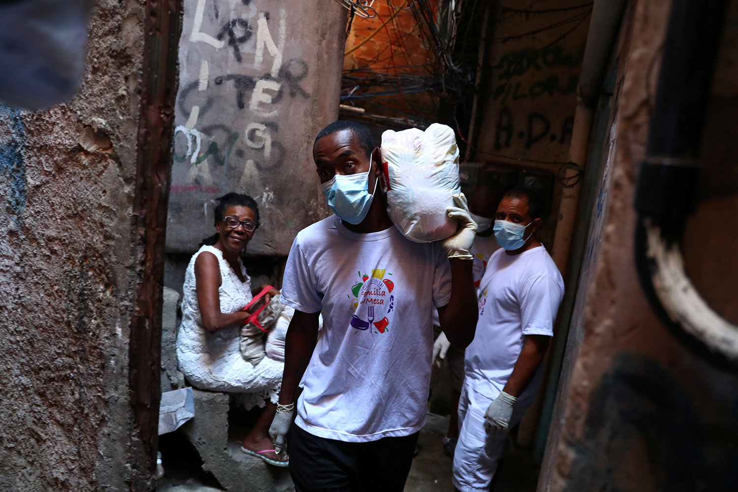 A volunteer carries donated aid for poor families at the Rocinha slum as the coronavirus disease (COVID-19) outbreak continues in Rio de Janeiro, Brazil March 27, 2020. REUTERS/Pilar Olivares