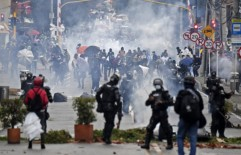 Demonstrators clash with riot police during a protest against a tax reform bill outside Colombian President Ivan Duque's house in Bogota on May 1, 2021. - Thousands of people demonstrated Saturday for the fourth consecutive day in Colombia to demand the withdrawal of a tax reform that, they claim, punishes the middle class in the midst of the pandemic. (Photo by Juan BARRETO / AFP)