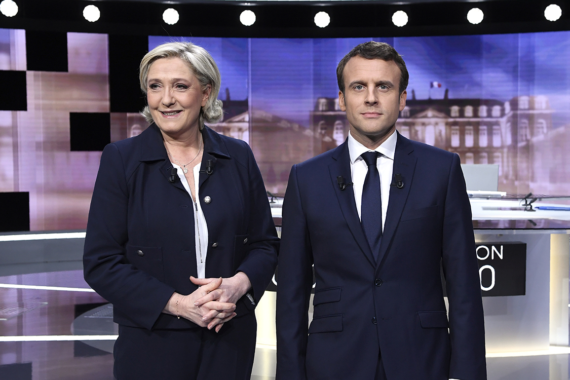 French presidential election candidate for the far-right Front National (FN) party, Marine Le Pen (L) and French presidential election candidate for the En Marche ! movement, Emmanuel Macron pose prior to the start of a live brodcast face-to-face televised debate in television studios of French public national television channel France 2, and French private channel TF1 in La Plaine-Saint-Denis, north of Paris, on May 3, 2017 as part of the second round election campaign. Pro-EU centrist Emmanuel Macron and far-right leader Marine Le Pen face off in a final televised debate on May 3 that will showcase their starkly different visions of France's future ahead of this weekend's presidential election run-off.  / AFP PHOTO / POOL / Eric FEFERBERG