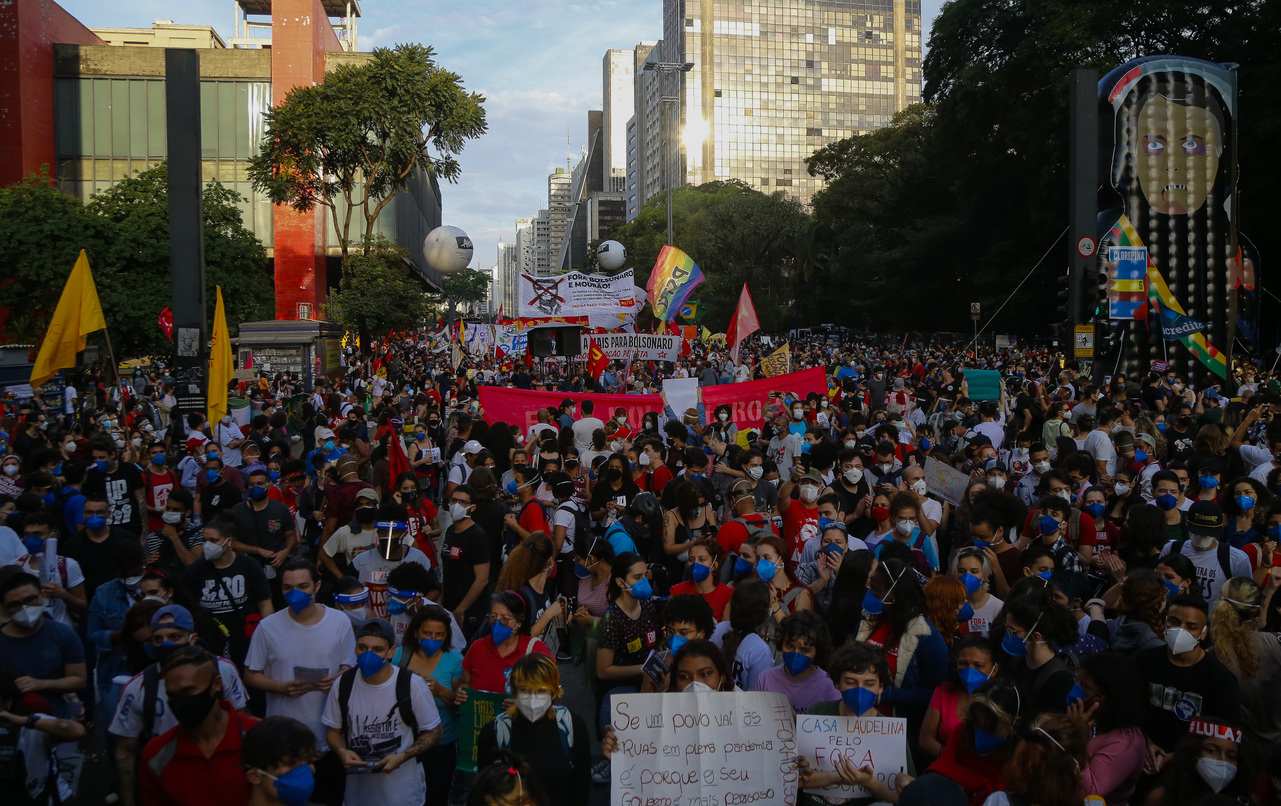SAO PAULO, BRAZIL - MAY 29: Demonstrators hold signs against Brazilian President Jair Bolsonaro as they gather during a protest against his government at Paulista avenue on May 29, 2021 in Sao Paulo, Brazil. Demonstrations against Jair Bolsonaro take place today in over 100 cities of Brazil. Brazilian president faces a probe carried by the Congress over his response to the pandemic. Protestors have a wide range of demands, including impeachment for Bolsonaro, increase of emergency economic aid, end of violence against black population and urgent arrival of vaccines to speed up inoculation. Brazil is being hit  hard by the third wave of the coronavirus pandemic and has reported over 457,000 deaths as cases continue to surge. (Photo by Miguel Schincariol/Getty Images)