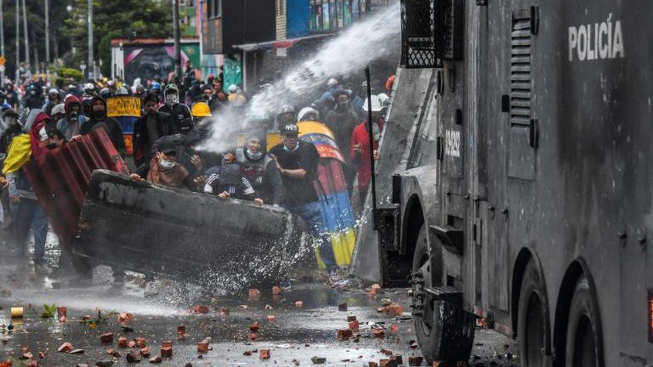 Police officers spray a water cannon at demonstrators during a protest in Bogota, Colombia, on June 9,