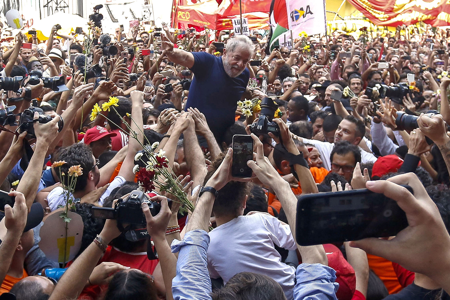 Brazilian ex-president (2003-2011) Luiz Inacio Lula da Silva is carried by supporters after attending a Catholic Mass in memory of his late wife Marisa Leticia, at the metalworkers' union building in Sao Bernardo do Campo, in metropolitan Sao Paulo, Brazil, on April 7, 2018. Brazil's election frontrunner and controversial leftist icon said Saturday that he will comply with an arrest warrant to start a 12-year sentence for corruption.