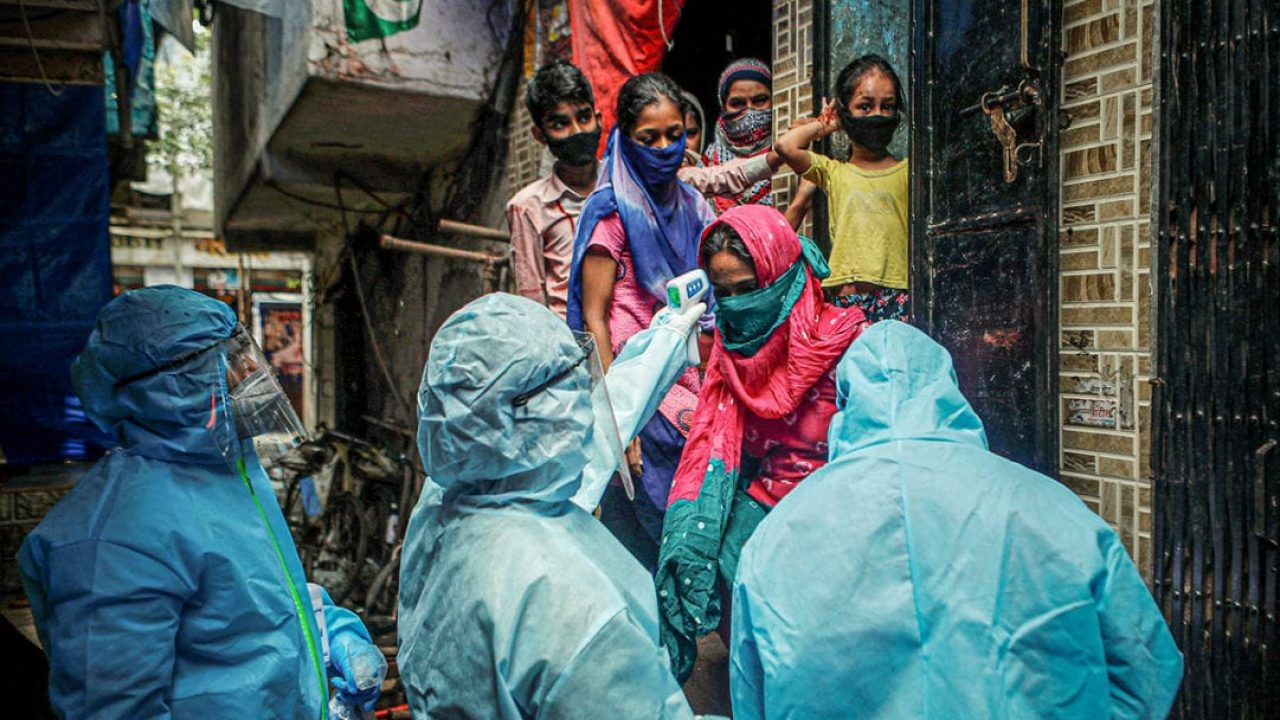 Healthcare workers wearing personal protective equipment (PPE) check the temperature of the residents of a slum during a check-up camp for the coronavirus disease (COVID-19) in Mumbai, India June 14, 2020. REUTERS/Francis Mascarenhas